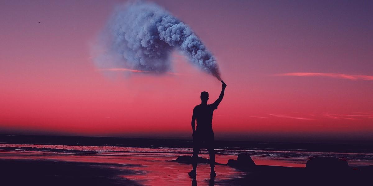 A man sprays gas on a beach