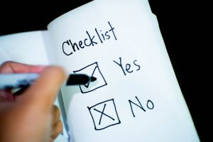 a yes or no check box on paper with a person holding a pen